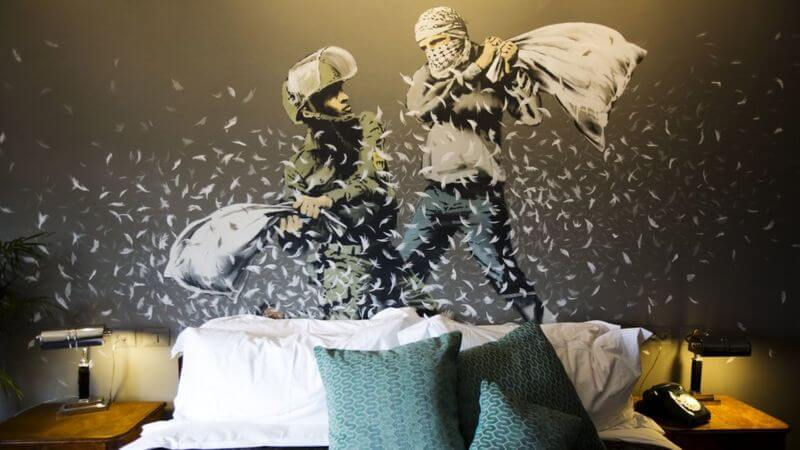 Banksy city guide 2021: Banksy, Pillow fight, 2017, Room of The Walled Off Hotel