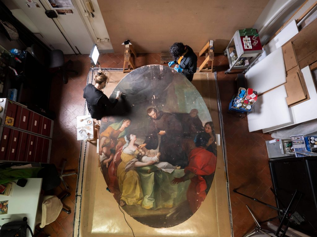 An aerial view of conservators in their studio with Saint John of God Heals Plague Victims. Francesco Cacchiani/Advancing Women Artists.