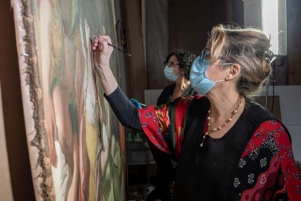 Conservators fill in the painting's missing areas of paint. Francesco Cacchiani/Advancing Women Artists.