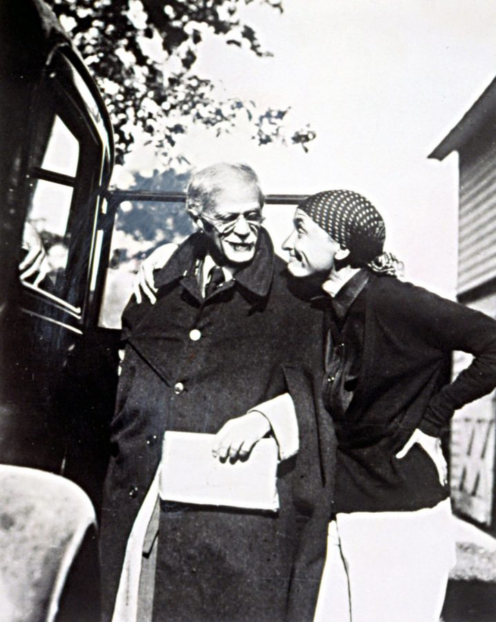Black and white photograph of Georgia O'Keeffe and Alfred Stieglitz in the streets. Stieglitz is wearing a large coat and is about to go in a car, his face directed to O'Keeffe who is smiling. She is wearing a scarf on her head, her right arm on Stieglitz's shoulder, the other and her hips.