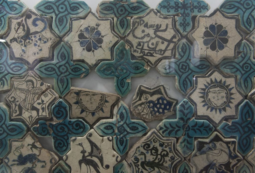 Mythical beasts, floral motifs, and figures on star and cross-shaped ceramic tiles