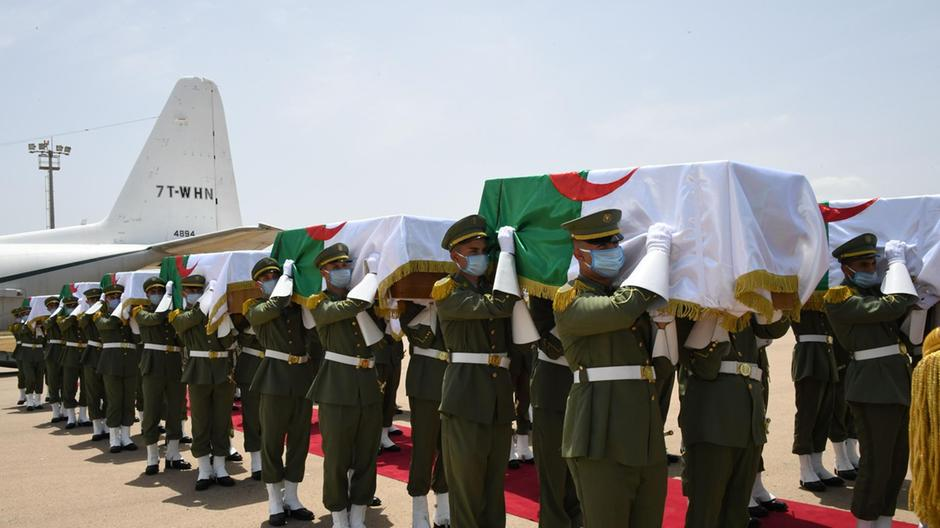 Return of Algerian Skulls: Photography of soldiers carrying coffins. The remains were flown in to Algiers on a Hercules C-130 transport plane, accompanied by Algerian fighters. AFP. The National News.