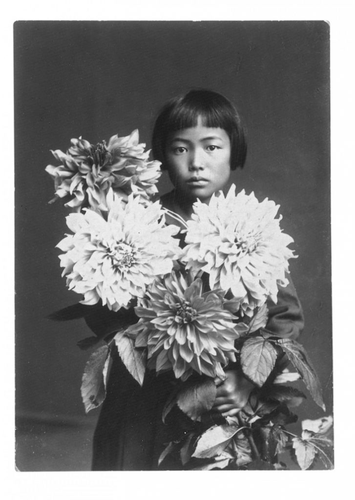 Black and White photograph of Yayoi Kusama as a child. She is wearing short square haircut. She holds a large bouquet of flowers that covers most of her kimono.