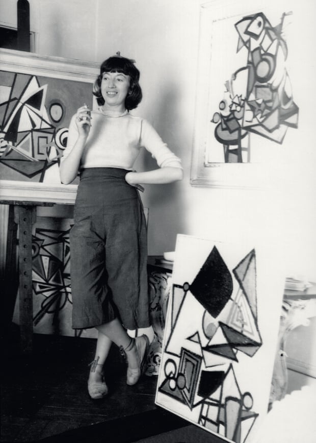 Black and whote photograph of Lee Krasner standing in her studio surrounded by her paintings.