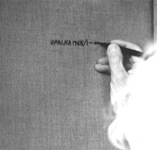 Roman Opałka signing the back of one of his