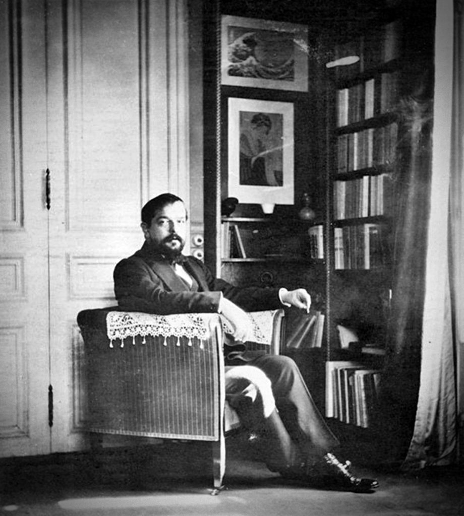 Claude Debussy in his Paris studio, 1910, photo, Debussy is sitting in his chair in the foreground, with print of the Great Wave hanging on the wall in the background