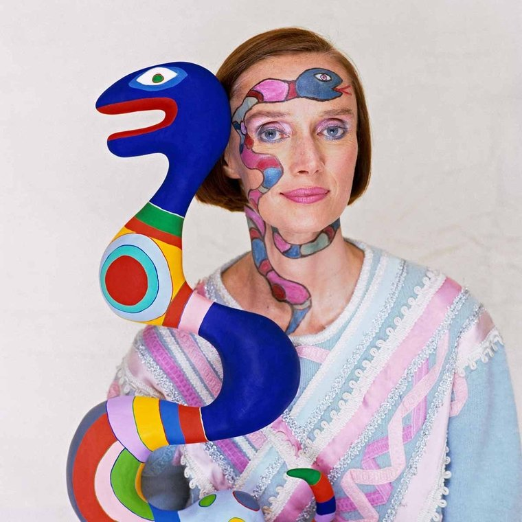 Niki de Saint Phalle, photographed with one of her iconic colorful sculptures in form of a snake.