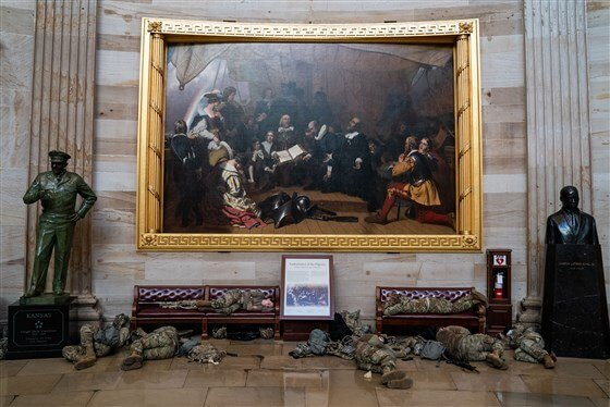 Recent image of US National Guard members resting in front of a painting in the rotunda of the United States Capitol Building surrounded by a statue and bust