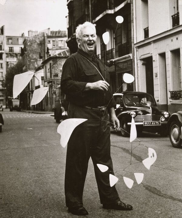 Jo's Art History Podcast. Alexander Calder, sculptor, Calder standing in street in Paris with one of his kinetic sculptures, art for all