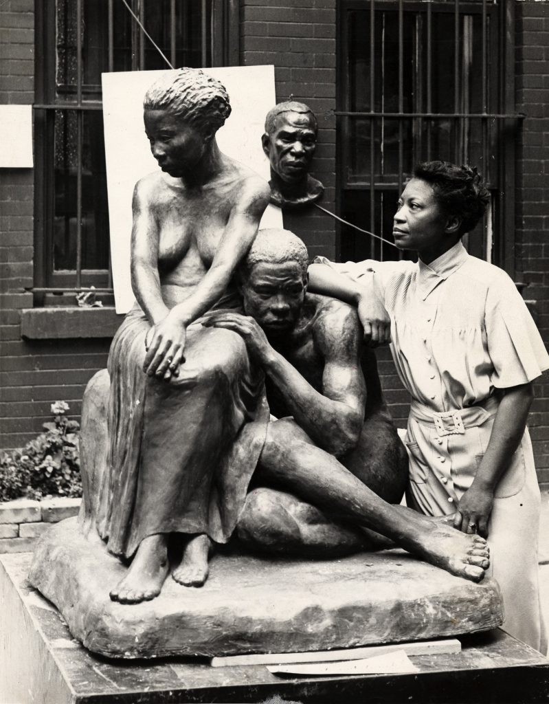 Great Women Sculptors. Photograph of Augusta Savage posing with her sculpture Realization, c.1938.