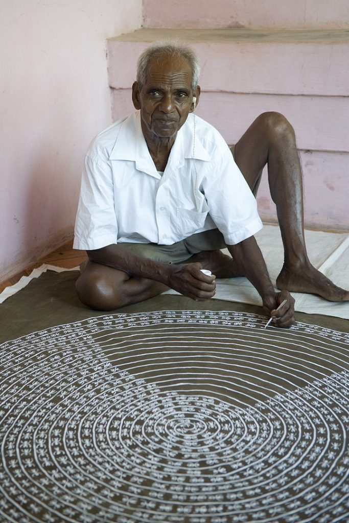 warli painting Jivya Soma Mashe at work in front of his house, 2009.
