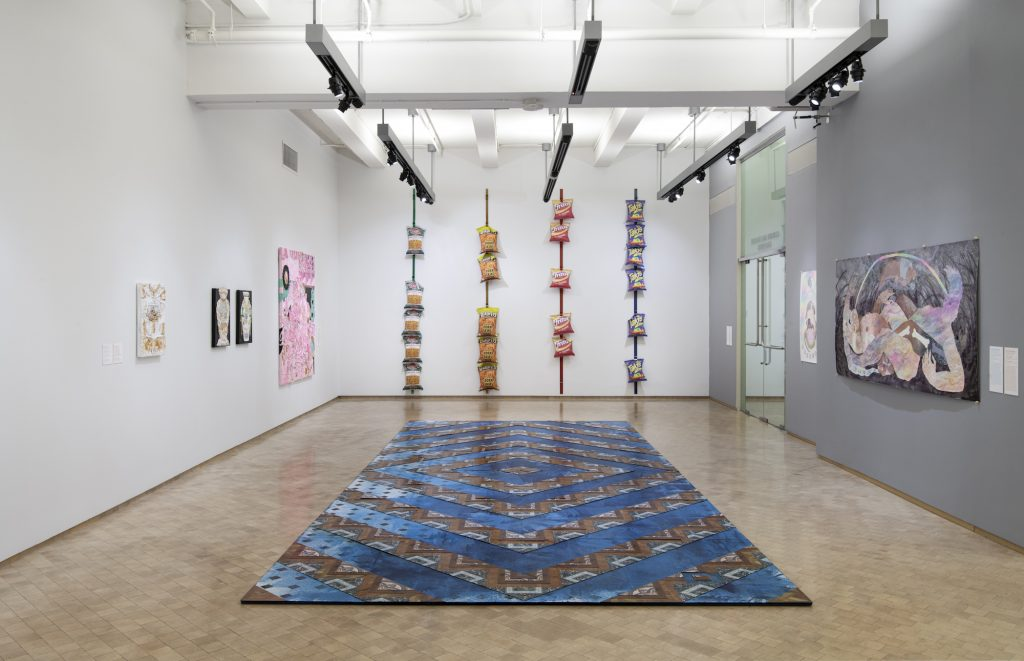 New York City Triennals 2021: Installation view of Estamos Bien - la Trienal 20/21 at El Museo del Barrio, New York, March 13 - September 26, 2021. Floor: Dionis Ortiz, Let There Be Light, 2020-2021. Enamel paint and vinyl tiles on wood; Back wall: Lucia Hierro, Rack: Platanitos, 2019, Rack: Chicharrones, 2019, Rack: Corn Chips, 2019, Rack: Takis, 2019; Right wall: Amaryllis DeJesus Moleski, The Trouble With Us (tropical storm), 2021; Amaryllis DeJesus Moleski, Exorcism, The Game, 2021; Left wall: Yvette Mayorga, The Procession (After 17th Century Vanitas) In loving memory of MM, 2020; Yvette Mayorga, A Vase of the Century 2 (After Century Vase c. 1876), 2019; Yvette Mayorga, American Urn # 4 (After Rocco Urn, 19th c.), 2019; Yvette Mayorga, A Vase of the Century 6 (After Century Vase c. 1876), 2019. Photograph: Martin Seck.