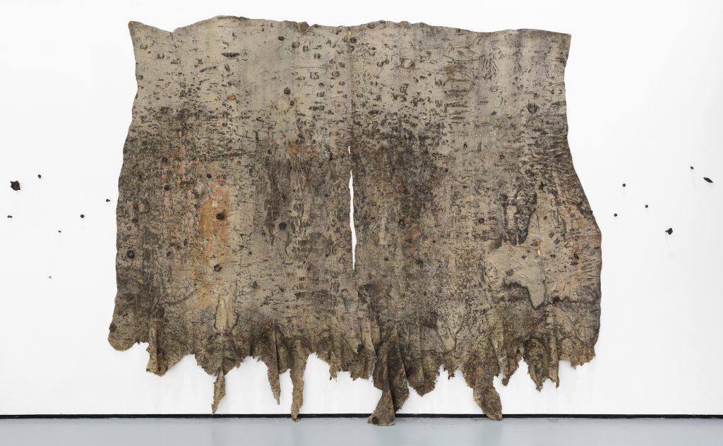 New York City Triennals 2021: Eddie R. Aparicio, City Bus Memorial (Fig. and Ave. 60, Los Angeles, California), 2016. Rubber, sulfur, tree and pain residue, resin, and ceramic on linen, 108 x 168 x 6 in. Courtesy the Artist. Photograph: Martin Seck.