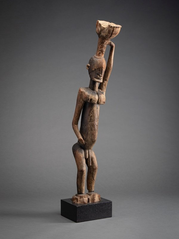 Dogon sculpture, Standing figure holding object above head, Dogon peoples, Mali, Bandiagara escarpment, 19th-early 20th century, carved wood, gift of Valerie Franklin, Courtesy San Diego Museum of Art, San Diego, CA, USA.
