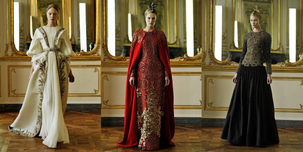 Three photographs of Alexander McQueen's Fall 2021 collection; right: cream dress with golden leaf embroideries, centre: red gown with golden embroderies and gems with a cape; left: black, long sleeve gown with goledn embroderies on the corest.