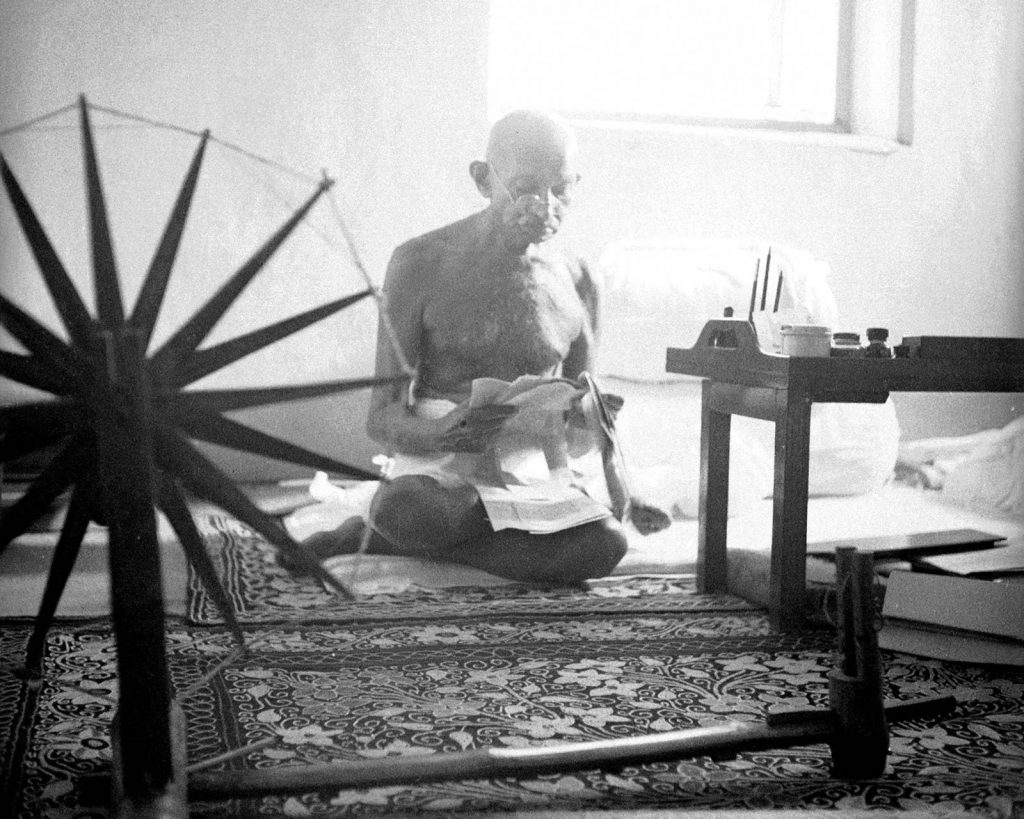 Margaret Bourke-White, Mohandas Gandhi reads as he sits cross-legged on the floor next to a spinning wheel at home, 1946. The LIFE Picture Collection via Getty Images.