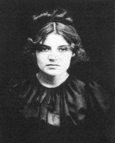 A black and white photograph of a white woman looking out at the camera. Her dark hair is pulled up and wears a dark colored dress.